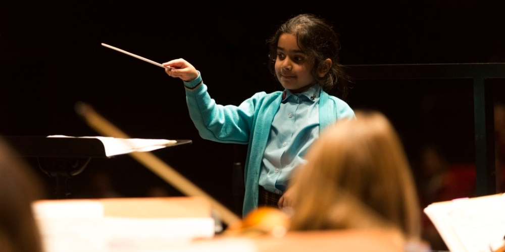 Image of a child conducting the orchestra.